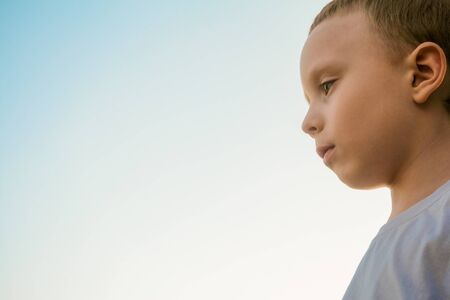Little boy looks down in front of him. Blue sky background with copy space. Foto de archivo