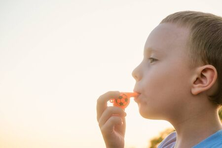 Little boy blowing in orange color whistle on a bright background of evening sunny sky