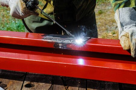 Welder welds steel profile. Mounting arc welding outdoors. Foto de archivo