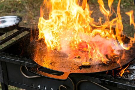 Burning food in a camping cast iron saj. Flame cover a metal dish on the grill with braised liver and vegetable roast.