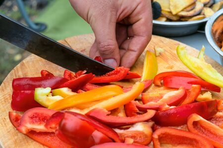 Knife slicing red and yellow sweet peppers on wooden cutting board