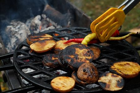Baked potatoes on a cast-iron grill grate. Pepper in grill tong. Foto de archivo