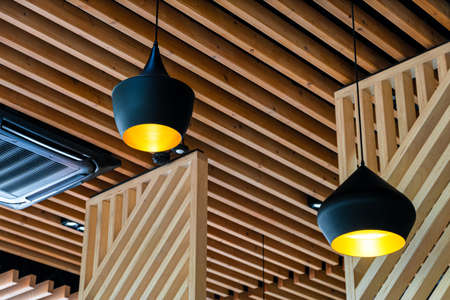 Two black pendant lamps in a wooden interior. Yellow lights hang overhead.