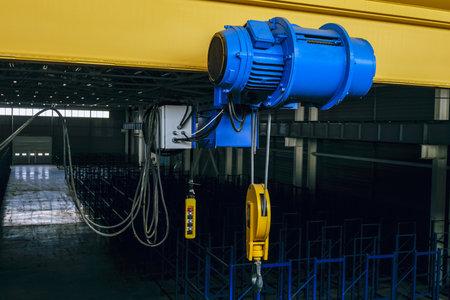 Overhead traveling cathead with steel hook in industrial engeenering plant shop