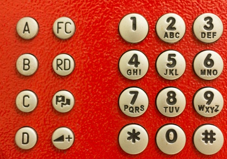 dial pad: A red public phone dial pad which has both number buttons and function buttons
