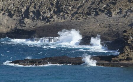 Blue ocean waves breaking on rocky coast photo