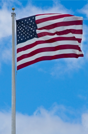 American flag blowing in the wind with a blue sky background photo