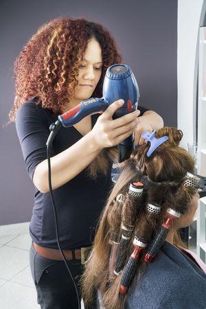Hair dresser applying rollers 1 photo