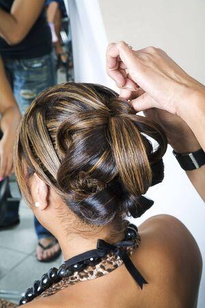 Hair dresser making an intricate hair do 1 photo