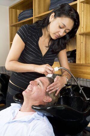 Hair desser washing a mans hair at the salon 1 photo
