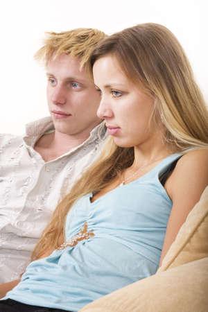 pareja viendo tv: Pareja joven mirando la televisi�n sentado en un sof�  Foto de archivo