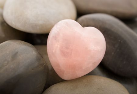 holistic: Rose quartz heart on pebbles