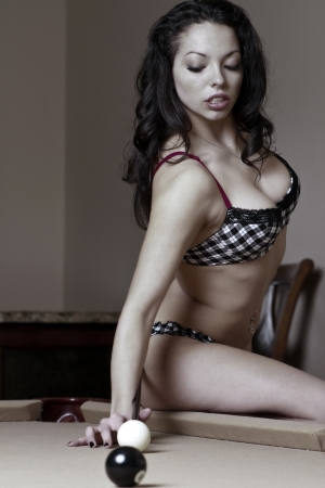 snooker cue: Sexy girl in bikini taking a difficult pool shot.