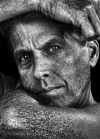 彼の腕で顔をフレーミング ハンサムな男の芸術的な肖像画