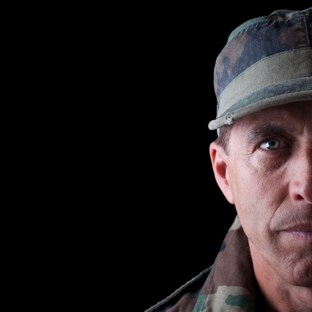 Army veteran portrait isolated on black background.