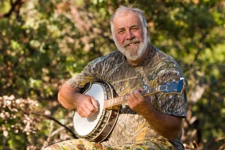 Happy senior playing the banjo outdoors