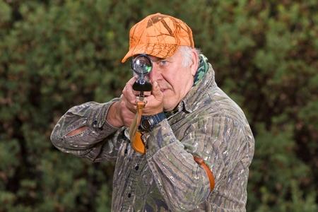 охотник: Старший охотник с винтовкой в руках в стрелковой позиции. Фото со стока