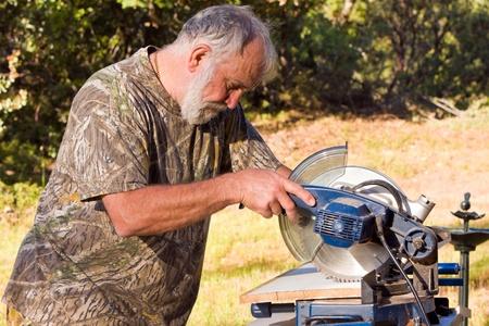 Actieve senior man buiten werken met een chop zag. Stockfoto