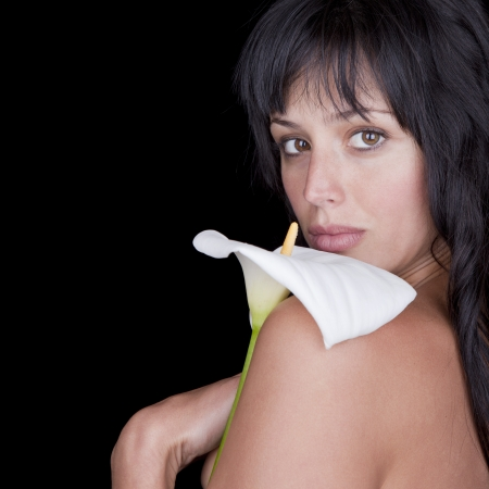 Beautiful young woman holding a calla flower over her shoulder. photo