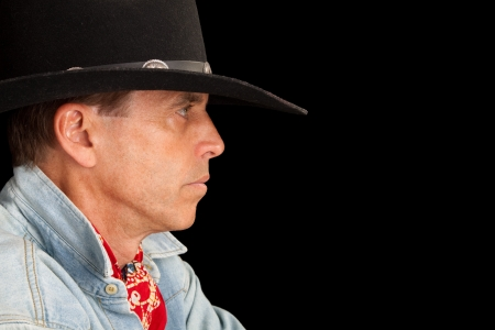 Closeup profile of a handsome man in a cowboy outfit. photo