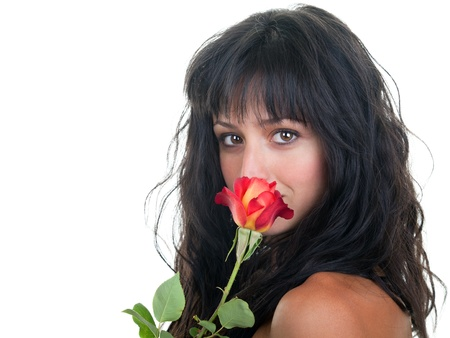 Beautiful young woman smelling a fresh red rose. photo