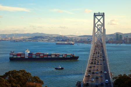 Freight ship passing under Bay Bridge, San Francisco Bay. photo