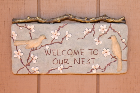 welcome home: Decorative wooden carving on a country home wall.