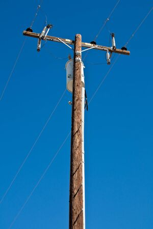 electric current: High voltage post against blue sky. Stock Photo