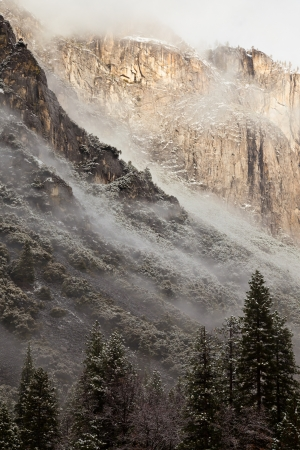 Dreamy winter landscape of clouds climbing up El Capitan in Yosemite National Park, California. photo