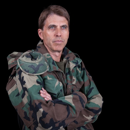 military man: Middle aged soldier with arms crossed, isolated on black.