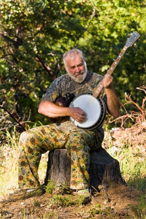 Senior man playing the banjo outdoors while hugging a moonshine jug  Stock Photo - 15044595