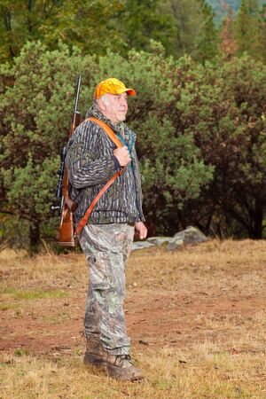 afield: Senior man standing in full hunting gear