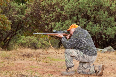 Senior hunter taking aim from a kneeling position