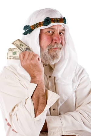 Older man in traditional Arab clothes holds hundred dollar bills  Stock Photo - 15044593
