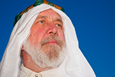 ethnic attire: Closeup portrait of an older Arab man isolated against blue sky  Stock Photo