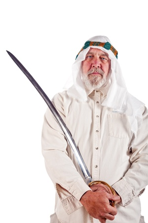 ethnic attire: Older Arab man posing with an antique sword.