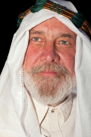Close-up portret van een oude Arabische man op zwart. Stockfoto
