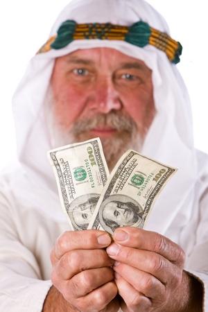 Senior Arab man offers US dollar banknotes. photo