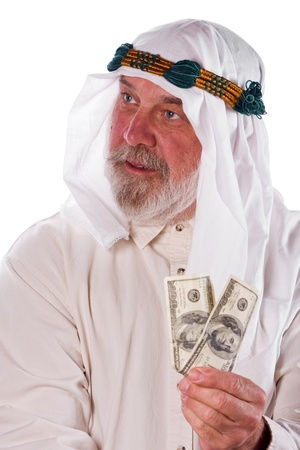 Older man in traditional Arab clothes holds up hundred dollar bills. photo