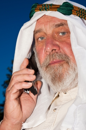 keffiyeh: Senior Arab man in traditional attire talking on a cell phone. Stock Photo