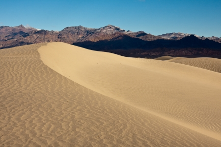 Sand dune and mountain range in Death Valley National Park, California.