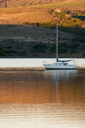 Boat at sunset anchored in Tomales Bay, California  Stock Photo