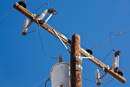 utility: High voltage post against blue sky. Stock Photo