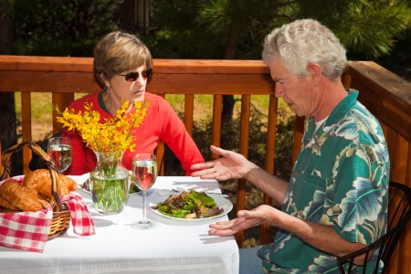 Middle aged man not happy with the salad he got served at an outdoor cafe. Stock Photo