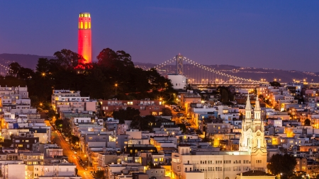telegraph hill: View of Coit Tower and St  Peter and Paul church at night, from Lombard street  Coit tower is lit red and gold in honor of the SF 49ers making the NFL playoffs  Stock Photo
