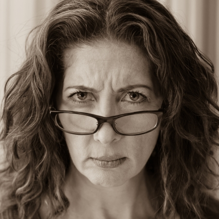 sceptical: Middle aged female teacher frowning over her glasses. Stock Photo