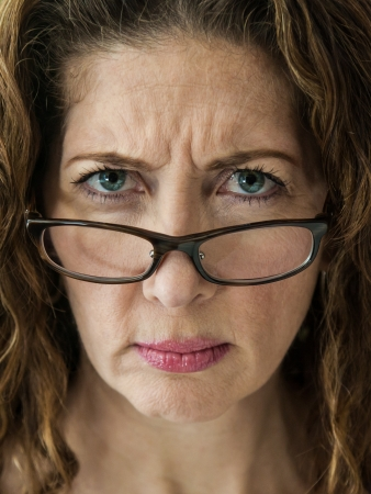 angry blonde: Middle aged female teacher frowning over her glasses. Stock Photo