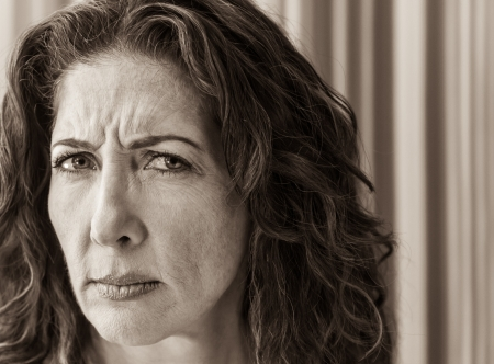 thinking woman: Middle aged woman frowning and looking askance at the viewer. Stock Photo