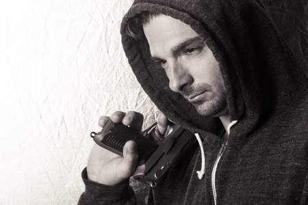 Black and white image of a caucasian male in a hoodie, holding a gun. photo