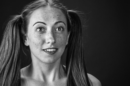 freckles: Cute freckled girl with pigtails on a gray background.